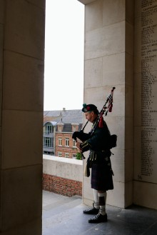 A lone bagpiper playing just inside the Memorial