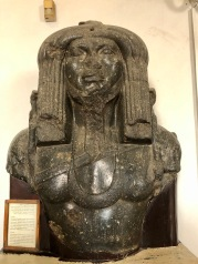 Large statue of Amenemhet III as a river god with thick hair wearing a panther skin